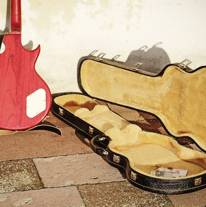 guitar case with coins and bills in vintage tone